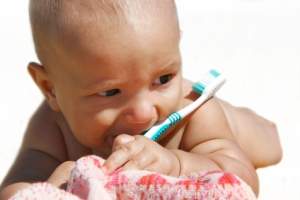 baby with toothbrush isolated over white