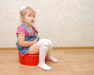 Pretty girl and red potty on wooden  floor